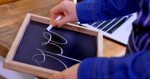 Female owner writing on chalkboard in cafe 4k Footage
