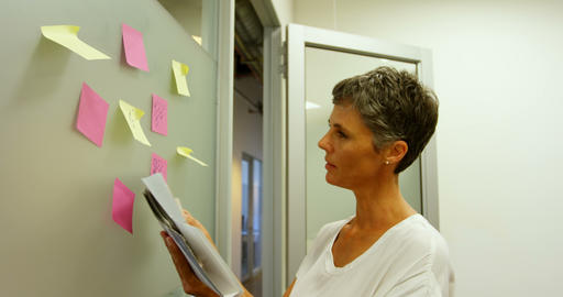 Businesswoman checking textile samples while looking at sticky notes 4k Live Action