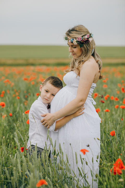 Young mother and her son walking on the poppy field Photo