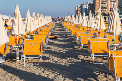 Rows of orange umbrellas and deckchairs on the beach Fotografía