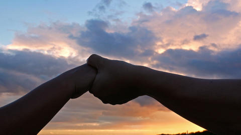 Close-up of boyfriend and girlfriend clasping each other hands in the evening Footage