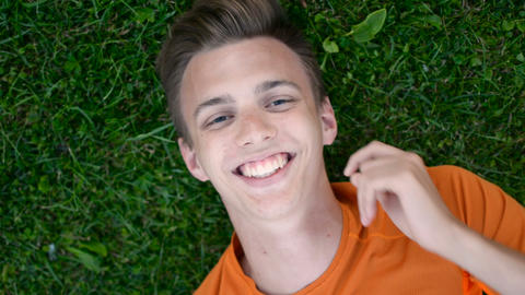 Top view of a teenage boy laying on the grass lawn resting and casually laughing Footage