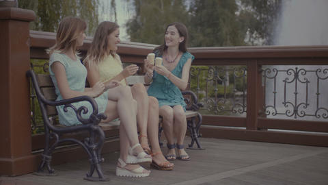 Three beautiful girlfriends eating ice cream on bench GIF