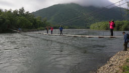 Travelers and tourists cross mountain river on suspension bridge. Time lapse GIF