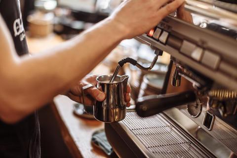 cropped side view photo of a coffee shop man preparing espresso Photo