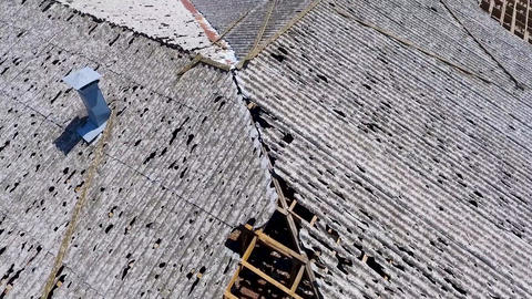 Roofs of houses damaged by hail. Consequences of hail in the village Live Action