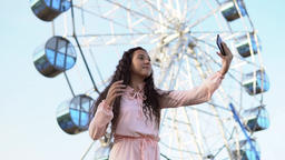 A young girl with long hair in a pink long dress makes selfie using a smartphone Footage