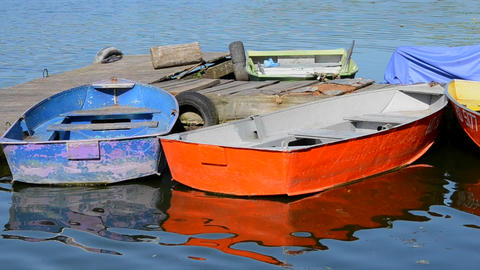 A few old shabby and worn boats different colors on the dock pier ビデオ