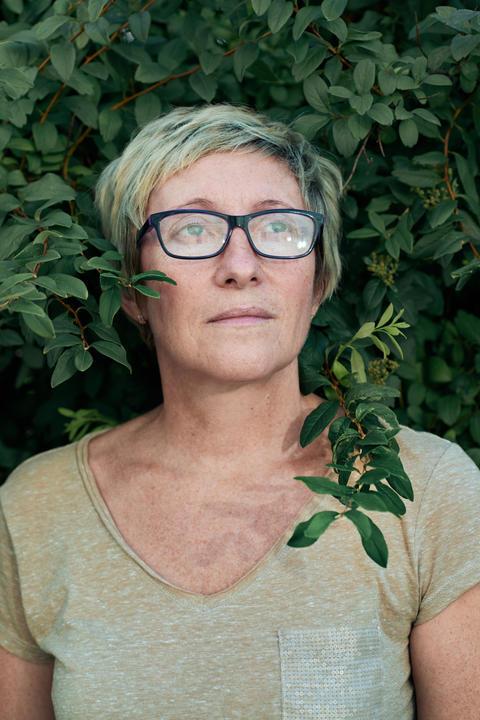 Aged lady near bush looking away Photo