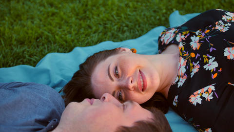Happy young adult couple lying on the grass over sunrise. Teal and orange Live Action