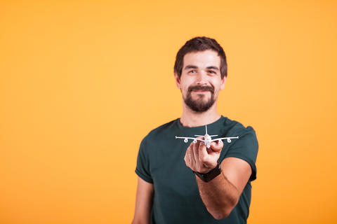 Happy smiling man showing a toy plane to the camera フォト