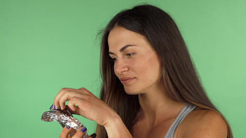 Young woman tasting dark chocolate, looking disappointed Footage