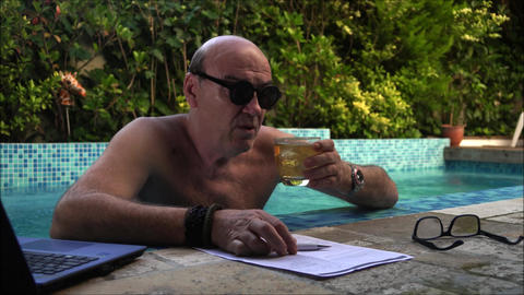 Balding company boss drinks whisky while working at his home / pool office ビデオ