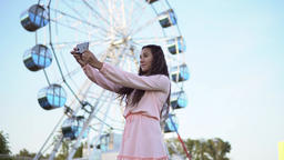 a girl with long hair in a pink long dress makes selfie using a smartphone while Footage