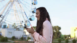 The girl walks by the ferris wheel and uses a smartphone. 4K 영상물