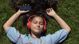 Young girl with long black hair listening to music on headphones lying on her Footage