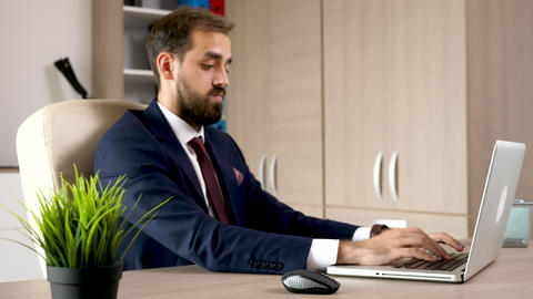 Young attractive entrepreneur in his office working on the computer Footage