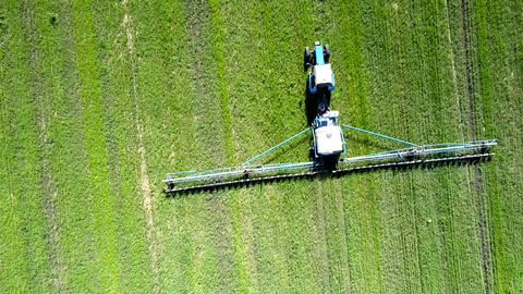 close vertical view tractor trailed sprayer drives on field Live Action