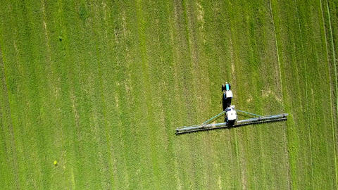 aerial view tractor trailed sprayer drives on field Live Action