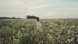Beauty girl with flower wreath on head running cross the flower field Live Action
