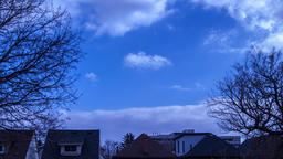 Time lapse of clouds with trees and roof tops of houses. Changing weather clouds Footage