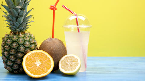 Coconut, sliced orange and lemon and a pineapple next to a plastic cup with Live Action