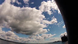 Time lapse of Clouds over water at a harbour. Large white fluffy clouds forming Footage