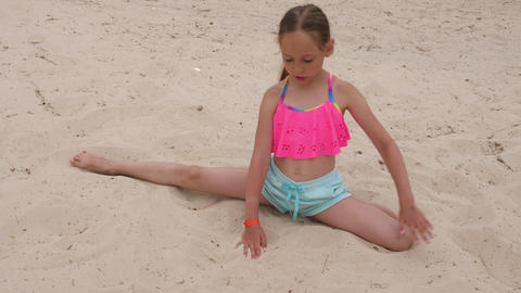 Young sportive girl doing right half split and stretching on sand Live Action