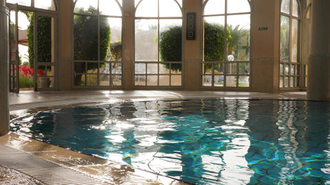 Empty indoor swimming pool with flares on water and windows Live Action
