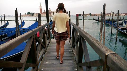 Girl walking in slow motion near gondolas in venice Live Action