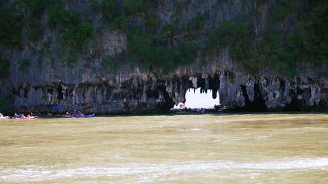 People kayaking near rocky shore ビデオ