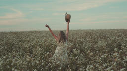 Beauty girl with a hat in her hand walks in a field with field flowers ビデオ