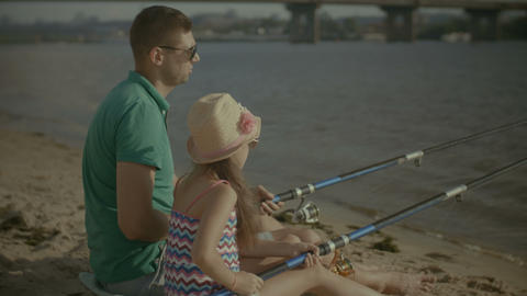 Father and cute girl fishing from shore on river Footage