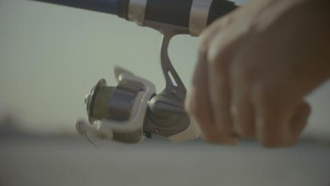 Fisherman hands twisting spinning reel ビデオ