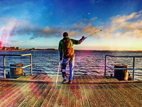 Hurt man on pier in the sunrise. The wharf construction above sea follow Sun Fotografía