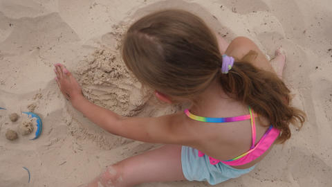 Girl teenager making sandy cake on summer beach at summer day top view Footage