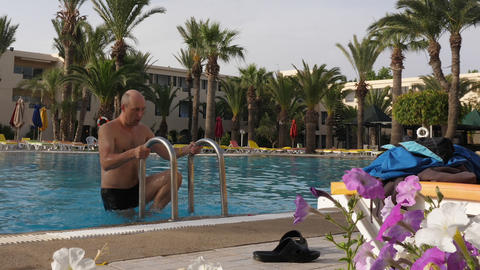 Man getting out of outdoor swimming pool in hotel on resort Footage