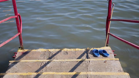 Blue slippers on the stairs that go into the sea Live Action