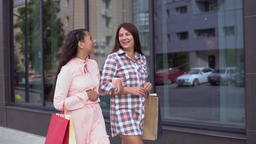 Two girls go after shopping holding shopping bags. slow motion Archivo