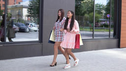 Two young happy girls go after shopping near the shopping center holding 영상물