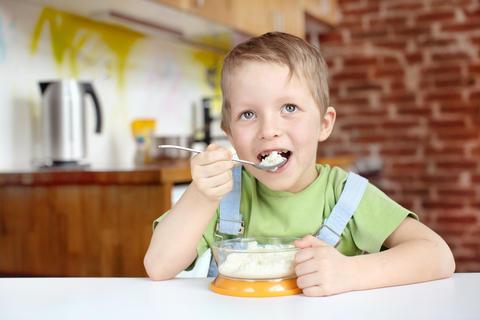 Little boy having breakfast in the kitchen Photo