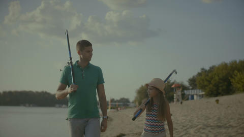Chatting family with fishing rods walking on beach Footage