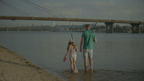 Family with fishing rods walking along riverbank Footage