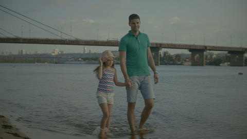 Carefree father and daughter walking on beach Footage