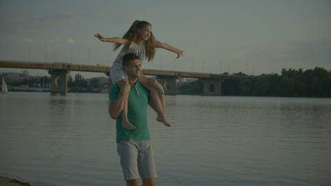 Little girl on dad shoulders outstretching her arms Footage