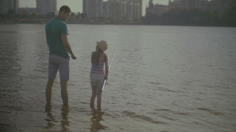 Caring father and cute daughter angling on river Footage
