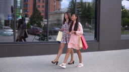 Two young girls in beautiful dresses go after shopping and carry shopping in 영상물