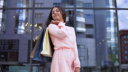 Girl in a dress after shopping with bags in hands. 4K Footage