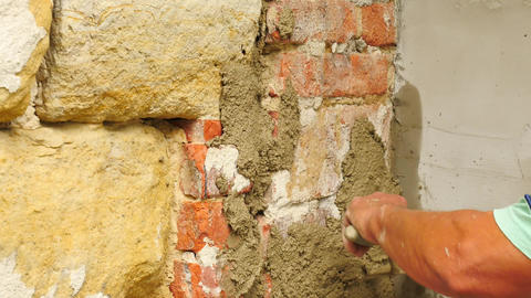 Detail of worker man hands putting fresh mortar on wall. Building stony and Footage