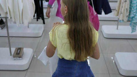 Blonde girl carrying clothes to fitting room in boutique GIF